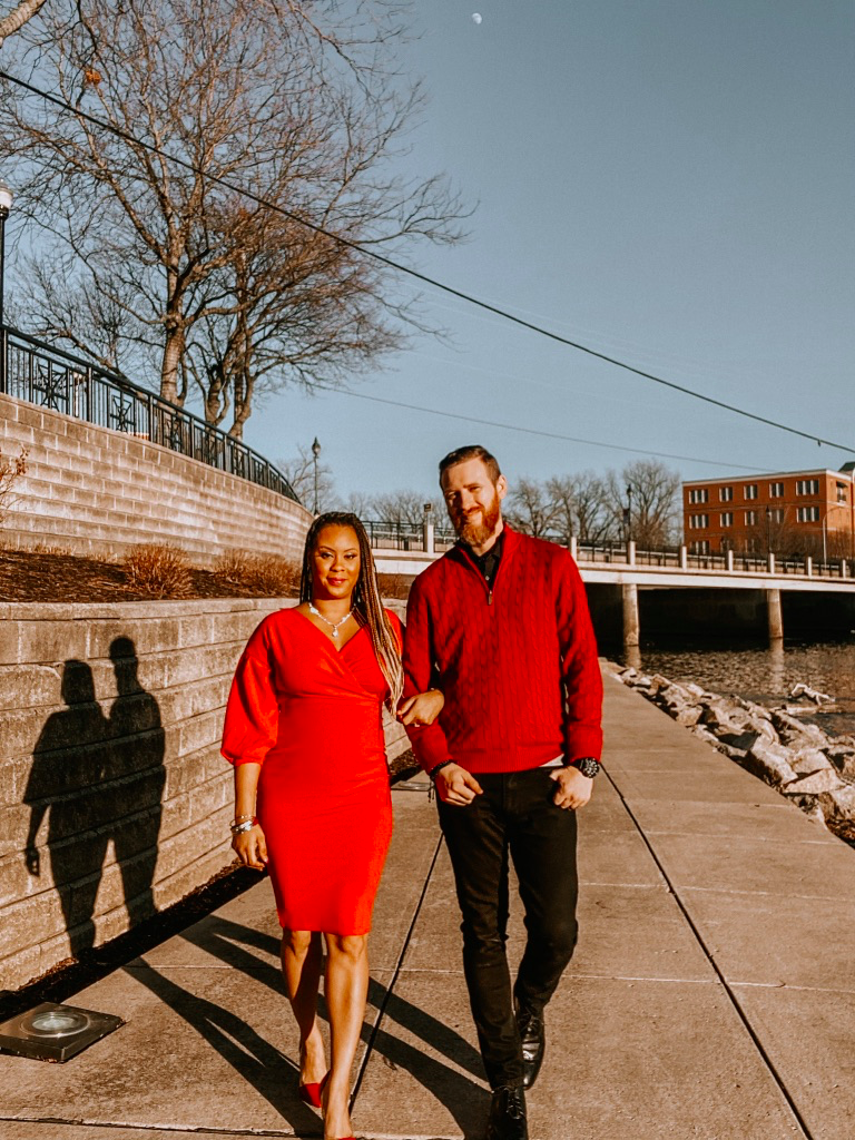 woman and man in red outfits standing outside posing for valentines day