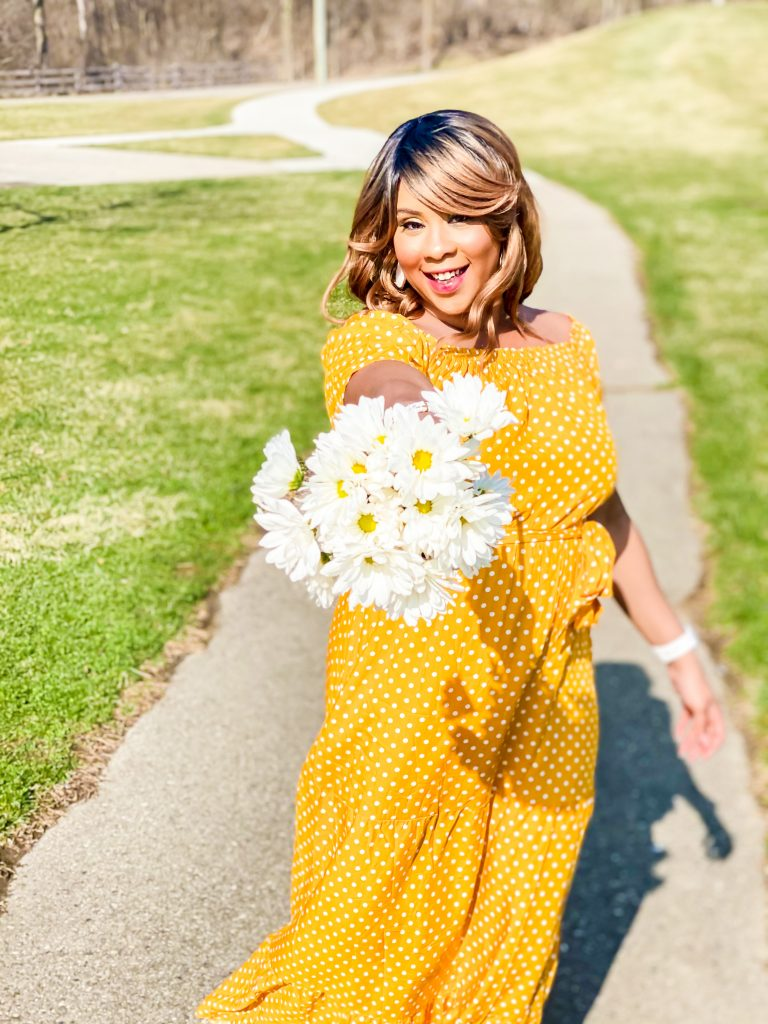 girl wearing yellow spring dress with white polka-dots. Girl holding flowers towards camera. Black girl in yellow polka-dot dress. Easter dress, spring fashion