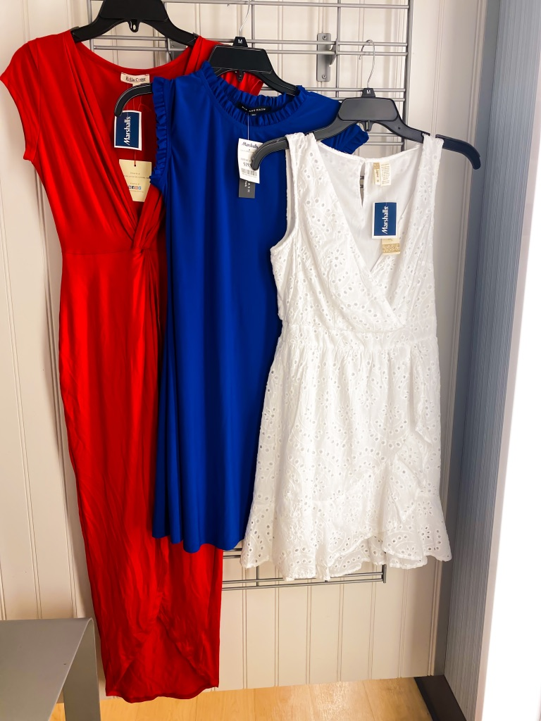 A picture of dresses hanging up in dressing room. Left to right is a red maxi dress with long v-neck, blue mini dress and a white dress. Fourth of july dresses.
