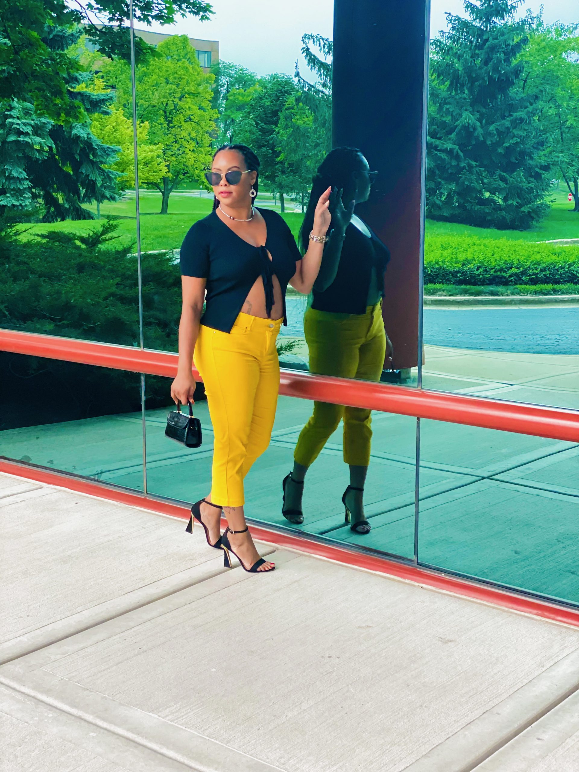 girl standing by glass window in black top and yellow capri pants