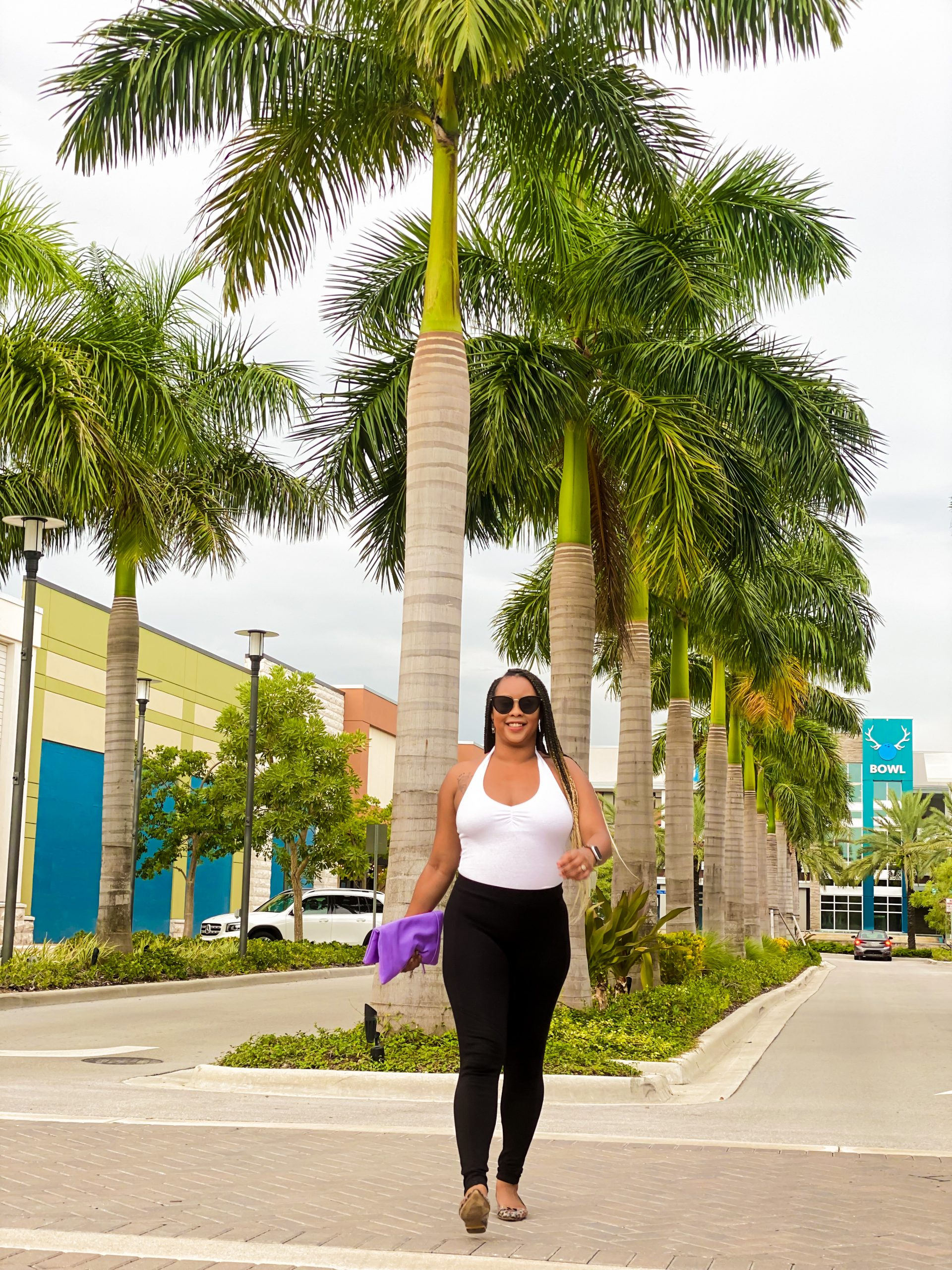 setitra standing in front of palm trees in street wearing black pants and a white halter top with black sunglasses on.