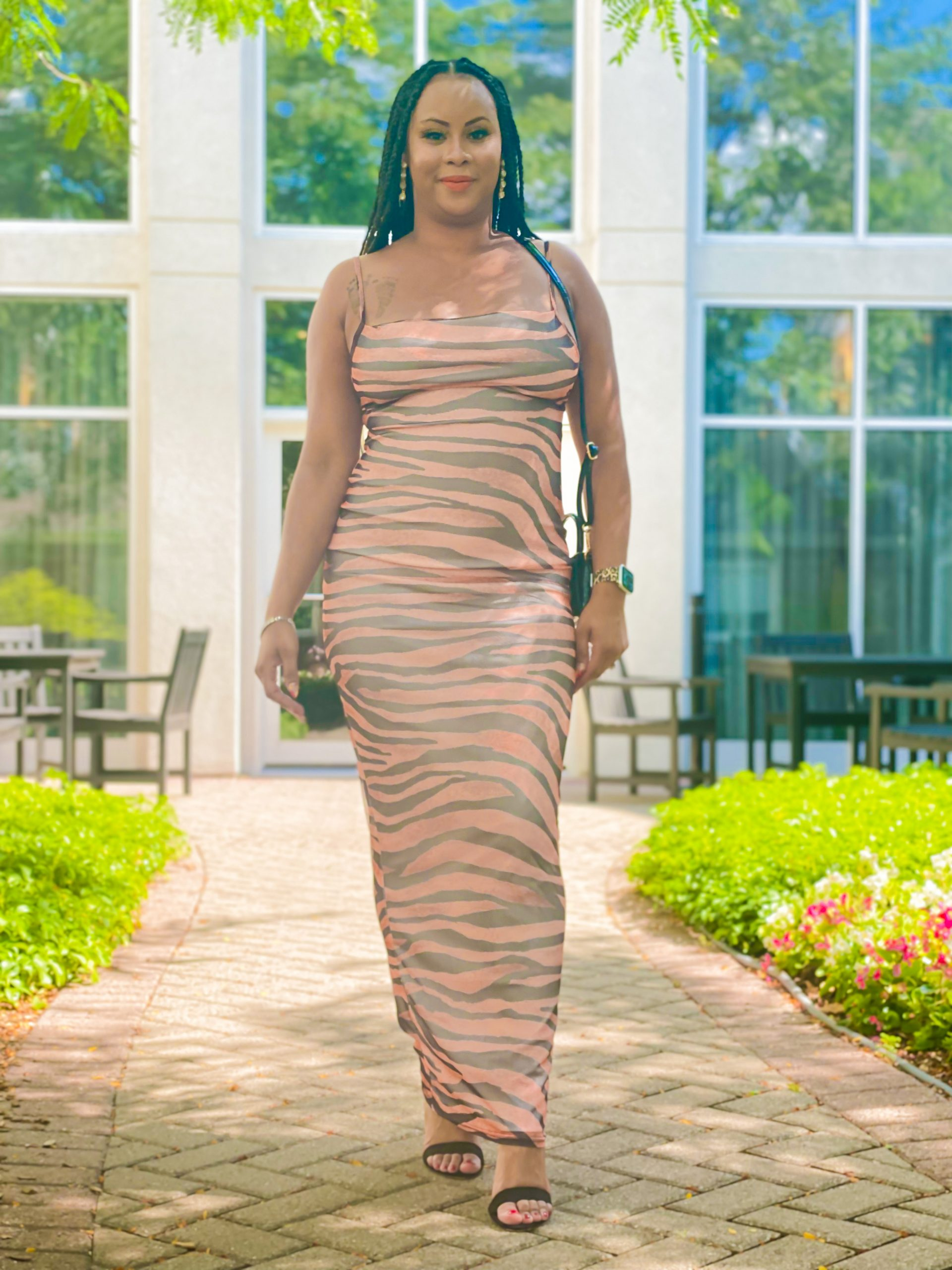 A black women in tiger mesh maxi dress, standing in front of glass building windows.