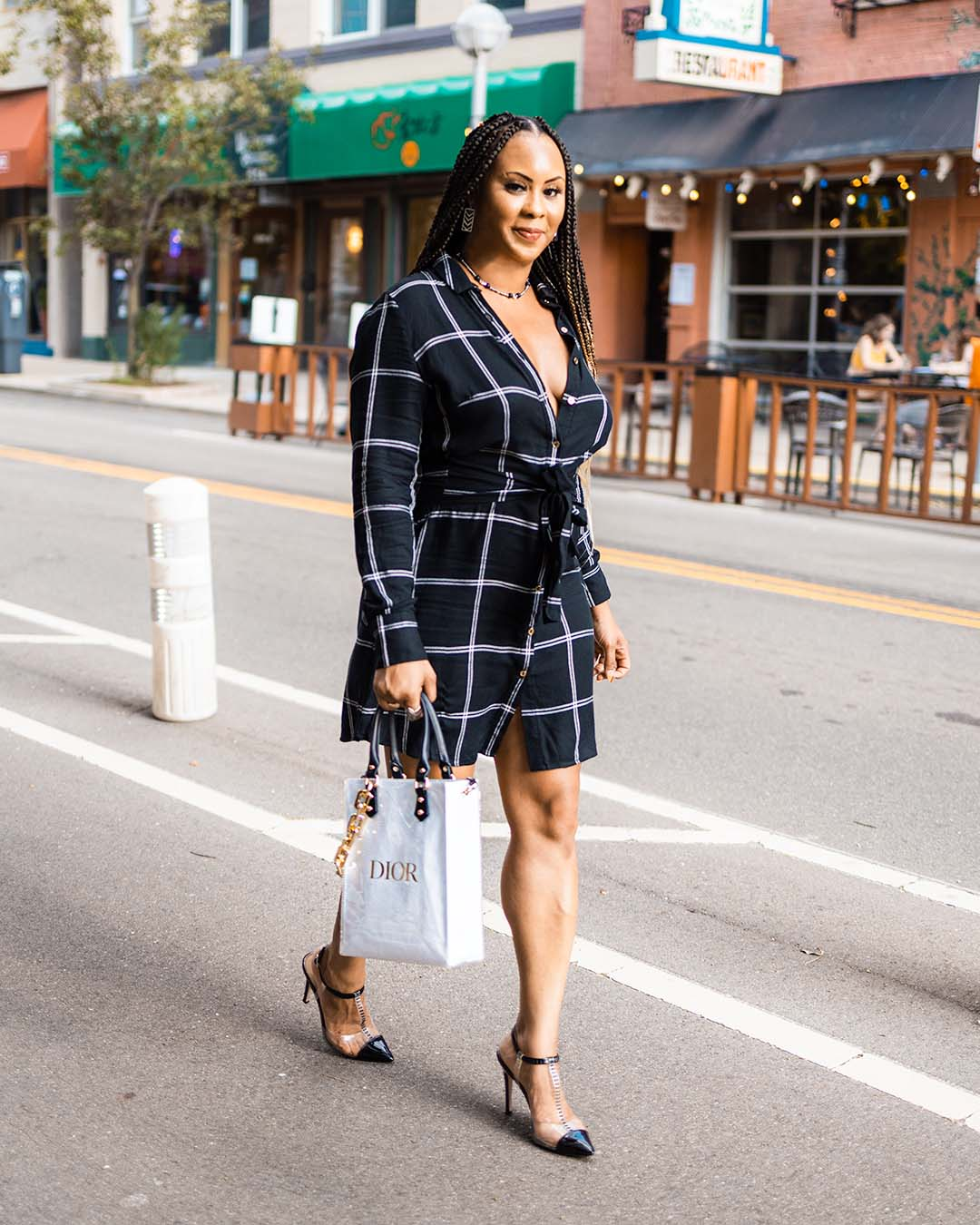 black girl walking in street with black and white stripe shirt dress, holding a Dior shopping bag and wearing black and clear high heels.