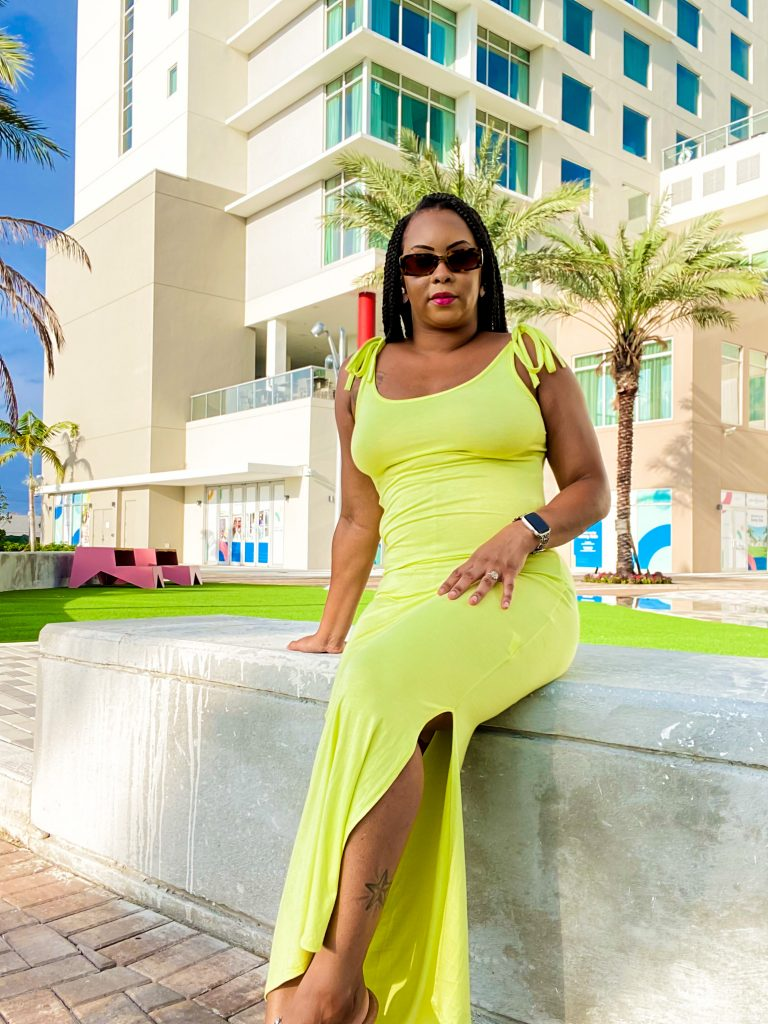 brown girl with braids, wearing a lime green maxi strap dress. She is sitting on cement bench in front of hotel building and palm trees with split dress showing calve and star tattoo. Girl is wearing brown retro rectangular sunglasses and apple watch on her left wrist.